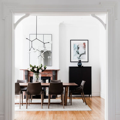 Example of a trendy light wood floor enclosed dining room design in Sydney with white walls, a standard fireplace and a stone fireplace