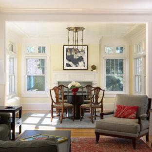 Ispirazione per una sala da pranzo aperta verso il soggiorno classica con pareti gialle, parquet chiaro, camino classico e cornice del camino piastrellata
