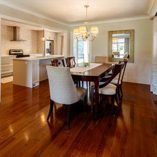 Cette image montre une salle à manger ouverte sur la cuisine traditionnelle de taille moyenne avec un mur beige, un sol en bois brun, aucune cheminée et un sol violet.