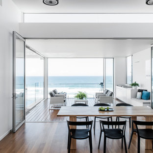 Inspiration for a contemporary dining room in Sunshine Coast with white walls, dark hardwood floors and brown floor.