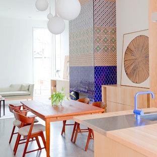 Exempel på en stor modern matplats med öppen planlösning, med vita väggar, betonggolv, en spiselkrans i trä och en bred öppen spis