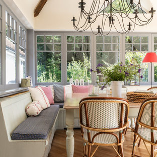 Design ideas for a large traditional kitchen/dining room in Surrey with beige walls, medium hardwood flooring and brown floors.