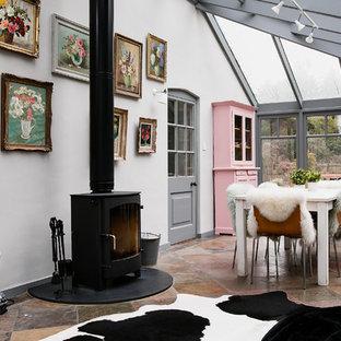 Идея дизайна: гостиная-столовая в стиле фьюжн с белыми стенами и печью-буржуйкой