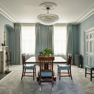 Large classic enclosed dining room in London with green walls, carpet, a standard fireplace, a stone fireplace surround and grey floors.