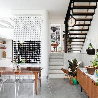 Modelo de comedor de cocina actual, de tamaño medio, sin chimenea, con paredes blancas, suelo de cemento y suelo gris