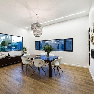 Foto de comedor de cocina moderno con paredes blancas, suelo de baldosas de porcelana, chimenea lineal, marco de chimenea de metal y suelo marrón