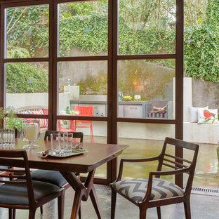 Immagine di una sala da pranzo aperta verso la cucina design di medie dimensioni con pavimento in cemento, pareti beige e nessun camino