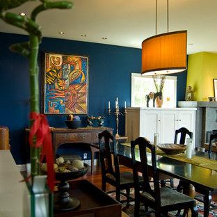 Modelo de comedor tradicional renovado con paredes azules, suelo de madera en tonos medios, chimenea tradicional, marco de chimenea de hormigón y suelo marrón