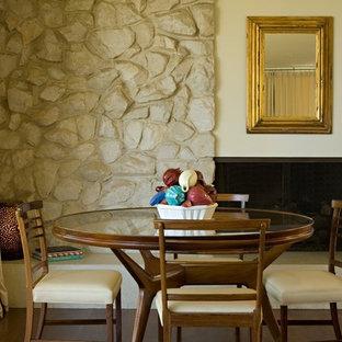 Diseño de comedor clásico renovado con paredes beige, suelo de madera oscura, marco de chimenea de piedra y chimenea lineal