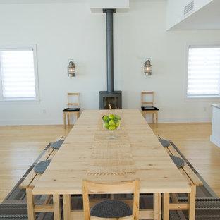 Idee per una sala da pranzo scandinava con pareti bianche, pavimento in legno massello medio e stufa a legna