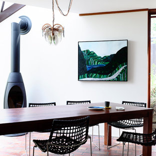 Inspiration pour une salle à manger bohème fermée et de taille moyenne avec un sol en brique, un poêle à bois, un mur blanc et un manteau de cheminée en métal.