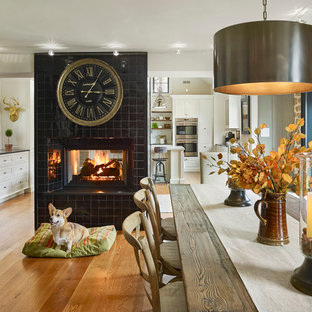 Inspiration for a large country kitchen/dining combo in Philadelphia with white walls, medium hardwood floors, a two-sided fireplace and a tile fireplace surround.