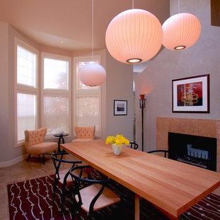 Idee per una sala da pranzo eclettica chiusa e di medie dimensioni con pareti grigie, pavimento in travertino, camino classico e cornice del camino piastrellata