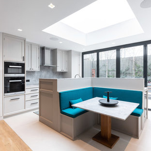 Contemporary kitchen/dining room in London with white walls and white floors.