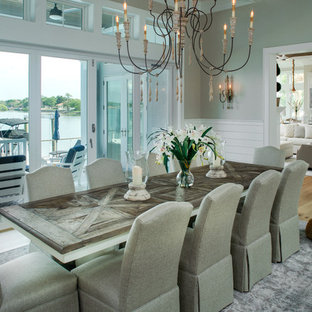 Coastal medium tone wood floor and brown floor enclosed dining room photo in Tampa with gray walls