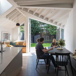 Foto di una sala da pranzo aperta verso la cucina design di medie dimensioni con pareti bianche, pavimento in gres porcellanato e pavimento nero