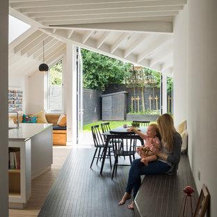 Ispirazione per una sala da pranzo aperta verso la cucina contemporanea di medie dimensioni con pareti bianche, pavimento in gres porcellanato e pavimento nero