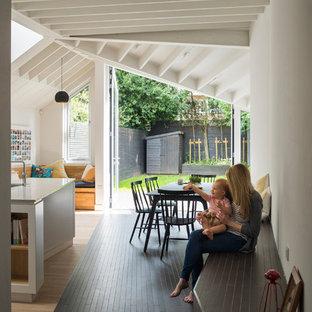 Ispirazione per una sala da pranzo aperta verso la cucina contemporanea con pareti bianche, pavimento in gres porcellanato e pavimento nero