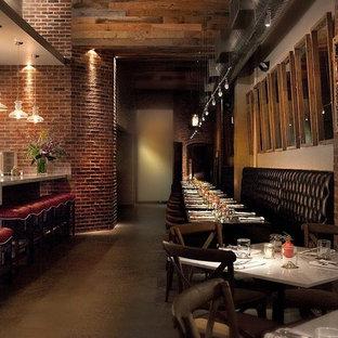 Immagine di un'ampia sala da pranzo aperta verso la cucina industriale con pareti bianche e pavimento in cemento