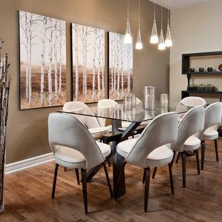 Foto di una sala da pranzo minimalista con pareti beige e pavimento in legno massello medio