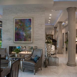 Esempio di una grande sala da pranzo aperta verso la cucina design con pareti bianche, pavimento in marmo, camino bifacciale e cornice del camino in pietra