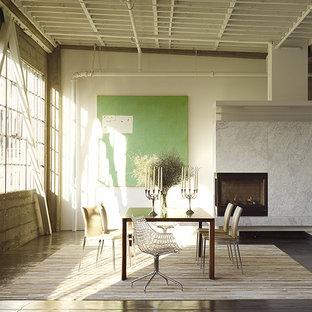 Diseño de comedor de cocina urbano, grande, con paredes blancas, suelo de cemento, chimenea de esquina, marco de chimenea de piedra y suelo gris