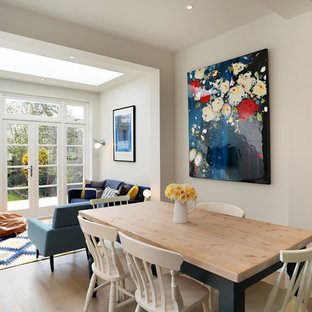 Classic open plan dining room in London with white walls, light hardwood flooring and brown floors.