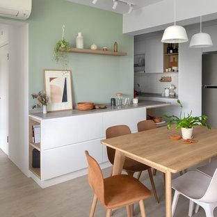 Modelo de comedor de cocina nórdico con paredes verdes, suelo de madera clara y suelo beige