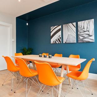 Immagine di una sala da pranzo aperta verso il soggiorno minimal di medie dimensioni con pareti multicolore, pavimento in laminato e nessun camino