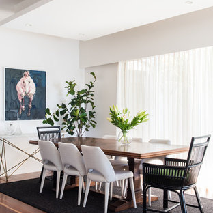This is an example of a transitional dining room in Brisbane with white walls, dark hardwood floors and brown floor.