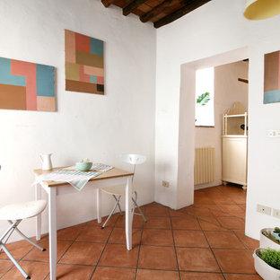 Réalisation d'une salle à manger méditerranéenne avec un mur blanc, un sol en carreau de terre cuite et un sol orange.