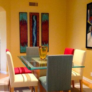 Modelo de comedor de cocina contemporáneo, pequeño, con paredes amarillas, suelo de madera clara, chimenea tradicional y marco de chimenea de baldosas y/o azulejos