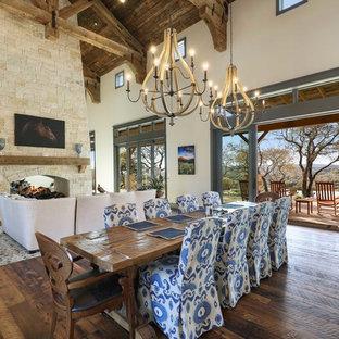 オースティンの巨大なラスティックスタイルのおしゃれなLDK (ベージュの壁、無垢フローリング、両方向型暖炉、石材の暖炉まわり、茶色い床) の写真