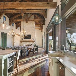オースティンの巨大なラスティックスタイルのおしゃれなダイニングキッチン (ベージュの壁、無垢フローリング、両方向型暖炉、石材の暖炉まわり、茶色い床) の写真