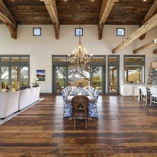 Ejemplo de comedor de cocina rústico, extra grande, con paredes beige, suelo de madera en tonos medios, chimenea de doble cara, marco de chimenea de piedra y suelo marrón
