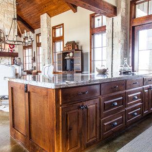 Modelo de comedor de cocina de estilo americano, de tamaño medio, con suelo de cemento, paredes beige, chimenea de doble cara y marco de chimenea de piedra