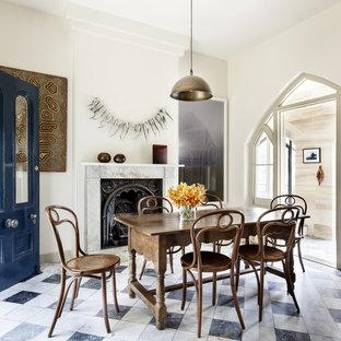 シドニーの中サイズのトラディショナルスタイルのおしゃれなダイニングキッチン (黄色い壁、大理石の床、薪ストーブ、石材の暖炉まわり、マルチカラーの床) の写真