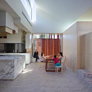 Diseño de comedor contemporáneo con paredes blancas y suelo de ladrillo