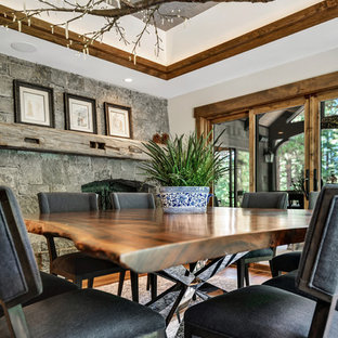 Example of a mid-sized mountain style medium tone wood floor and brown floor enclosed dining room design in Other with gray walls, a two-sided fireplace and a stone fireplace
