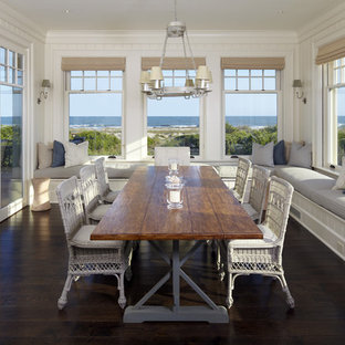 Example of a coastal dark wood floor and brown floor dining room design in Charleston with white walls