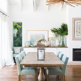 Idee per una sala da pranzo aperta verso il soggiorno costiera con pareti bianche, pavimento in legno verniciato, camino classico e pavimento marrone