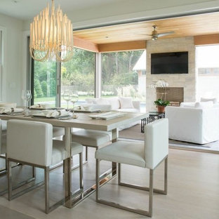 Example of a trendy light wood floor dining room design in New York with white walls