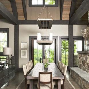 Immagine di una grande sala da pranzo aperta verso il soggiorno stile rurale con pareti bianche, parquet chiaro, camino bifacciale e cornice del camino in pietra