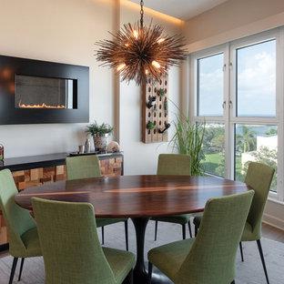 Immagine di una sala da pranzo aperta verso la cucina chic di medie dimensioni con camino sospeso, pavimento in gres porcellanato, cornice del camino in metallo e pavimento marrone