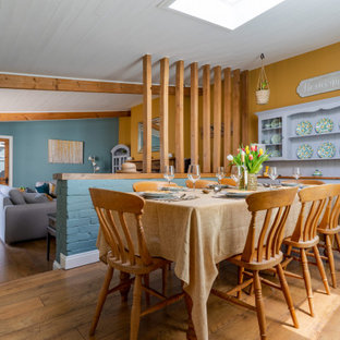 Design ideas for a medium sized classic enclosed dining room in Devon with yellow walls, medium hardwood flooring and brown floors.