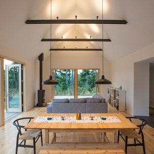 Modelo de comedor rural, pequeño, abierto, con paredes blancas, suelo de madera clara y estufa de leña