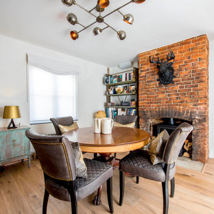 Inspiration for an eclectic dining room in Hampshire with white walls, light hardwood flooring, a standard fireplace, a brick fireplace surround and brown floors.