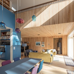 Ispirazione per una sala da pranzo minimal di medie dimensioni e chiusa con pareti blu, parquet chiaro, cornice del camino in mattoni, pavimento beige e stufa a legna