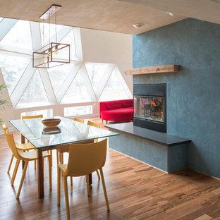 Свежая идея для дизайна: огромная гостиная-столовая в современном стиле с синими стенами, полом из бамбука и фасадом камина из металла - отличное фото интерьера