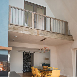 Esempio di un'ampia sala da pranzo aperta verso il soggiorno design con pareti blu, pavimento in bambù e cornice del camino in metallo